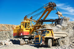 Excavator loading granite or ore into dump truck at opencast Royalty Free Stock Photos
