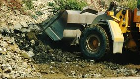 Excavator loading granite stones in the quarry.