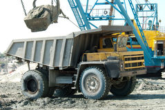 Excavator loading a heavy dump truck Stock Images