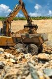 Excavator loading heavy duty dumper truck with rocks Royalty Free Stock Image
