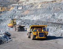 Excavator loading iron ore into heavy dump trucks. On the opencast mining site stock photo