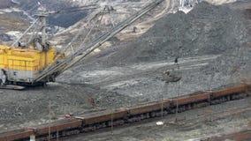 Excavator loading of iron ore on train stock video