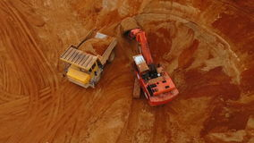 Excavator loading mining truck at sand quarry. Sand mining industry. Excavator loading mining truck at sand quarry. Drone view of mining machinery working at stock footage