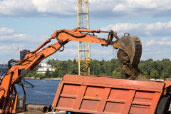 Excavator loading sand on dumper truck Stock Photos