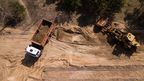 Excavator loading sand into a truck with aerial photography drone. royalty free stock image