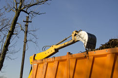 Excavator loading soil into dumper truck Royalty Free Stock Image