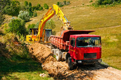 Excavator loading soil on a truck while building a road Stock Image