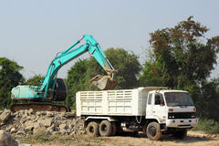 Excavator loading stone dump truck Royalty Free Stock Photos
