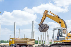 Excavator is loading a truck on building site Stock Photo