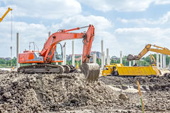 Excavator is loading a truck on building site Stock Photography