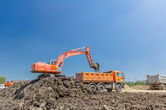 Excavator is loading a truck on building site. Big excavator is filling a dump truck with soil at construction site, project in progress Royalty Free Stock Image