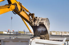 Excavator loading truck at building site Stock Images