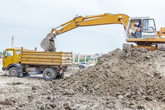 Excavator is loading a truck on building site Royalty Free Stock Photo