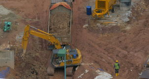 Excavator loading truck on construction site. Works on construction site. Excavator loading dump truck with ground stock footage