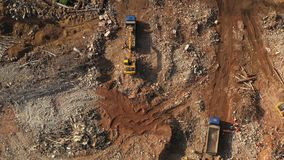 Excavator loading a truck after demolishing houses. Aerial top view. Excavator loading a dump truck after demolishing houses. Aerial top view stock footage
