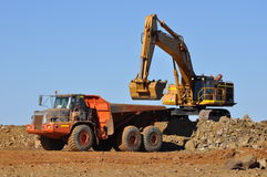 Mining Excavator loading truck in mine quarry Stock Images