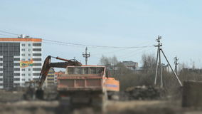 Excavator loads the clay into the trucks. At a construction site stock footage
