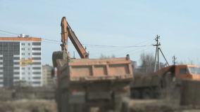 Excavator loads the clay into the trucks. At a construction site stock video