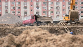 Excavator loads clay using bucket into dump truck. MOSCOW, RUSSIA - JULY 07, 2017: Yellow excavator loads clay using its big bucket into the dump truck on the stock video