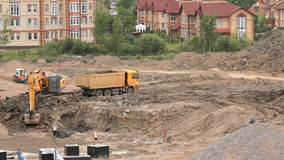 Excavator loads clay using bucket into dump truck. MOSCOW, RUSSIA - JULY 07, 2017: Yellow excavator loads clay using its big bucket into the dump truck on the stock footage