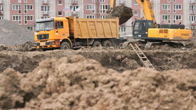 Excavator loads clay using bucket into dump truck. Moscow, Russia - July 07, 2017: Yellow excavator loads clay using its big bucket into the dump truck on the stock video footage