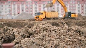 Excavator loads clay using bucket into dump truck stock footage