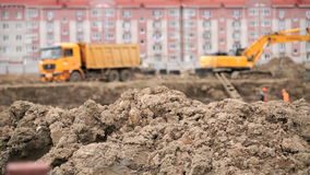 Excavator loads clay using bucket into dump truck. Yellow excavator loads clay using its big bucket into the dump truck on the background residential development stock footage