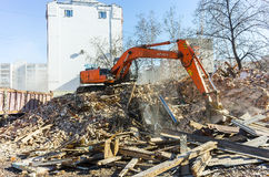 Excavator loads garbage from demolished house Stock Photo