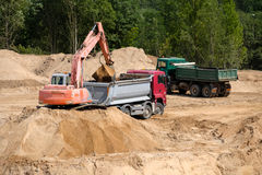Excavator loads the ground in the truck Royalty Free Stock Photography