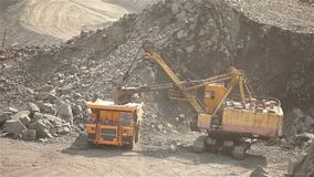 The excavator loads the ore in a mining dump truck, excavator and dump truck in the iron ore quarry. The excavator and dumper in the quarry, the excavator pours stock video