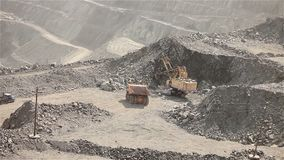 The excavator loads the ore in a mining dump truck, excavator and dump truck in the iron ore quarry. The excavator and dumper in the quarry, the excavator pours stock footage