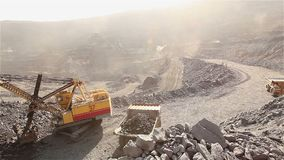 The excavator loads the ore in a mining dump truck, excavator and dump truck in the iron ore quarry panorama. The excavator and dumper in the quarry, the stock footage
