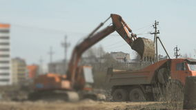 Excavator loads soil into a truck at construction stock video