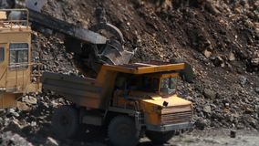 Excavator loads a stone in the heavy truck in the quarry mining granite stock footage