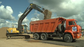 Excavator loads a truck with gravel stock video