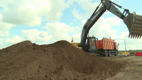 Excavator loads a truck with gravel stock footage