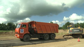Excavator loads a truck with gravel stock video footage