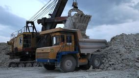 Excavator loads a truck rock in the quarry. Excavator loads a truck rock the quarry stock video