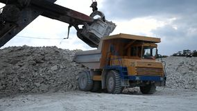 Excavator loads a truck rock in the quarry stock video