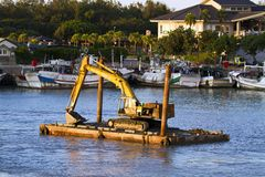 Excavator machine construct on sea Royalty Free Stock Images