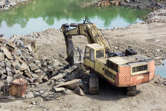 Excavator machine doing earthmoving work. Track-type loader excavator machine doing earthmoving work at basalt quarry stock photography