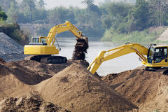 Excavator machine group works at river Royalty Free Stock Photography