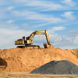 Excavator machine loading dumper truck at sand quarry Royalty Free Stock Images