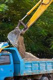 Excavator machine loading soil or sand into truck body Stock Photography
