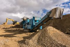 Excavator and machine to pulverize stone in a quarry stock photo