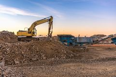 Excavator and machine to pulverize stone in a quarry royalty free stock photography
