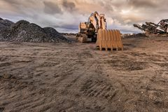 Excavator and machine to pulverize stone in a quarry royalty free stock images