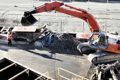 Excavator machinery. Construction workers moving steel plates Stock Photos