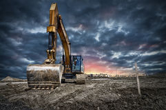 Excavator machinery at construction site. Sunset in background Stock Image