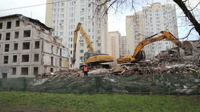 Excavator machinery working on demolition old house stock footage